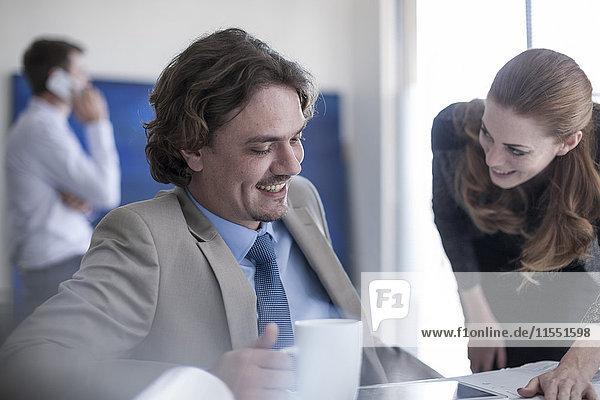 Lächelnder Geschäftsmann und Frau am Schreibtisch beim Reden