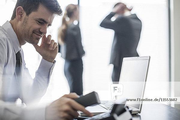 Lächelnder Geschäftsmann im Büro mit Laptop und Telefon