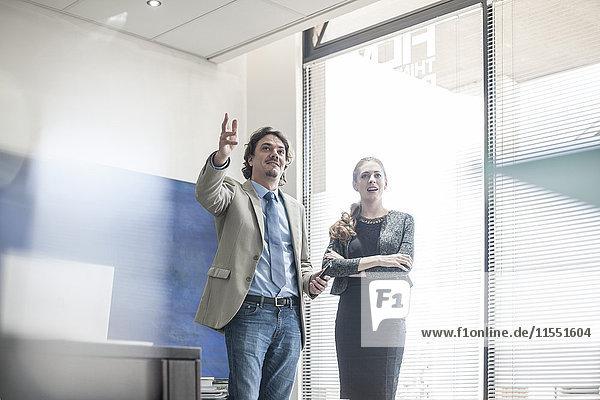 Geschäftsmann und Frau im Gespräch am Fenster