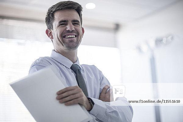 Lachender Geschäftsmann mit Papieren