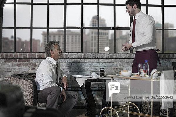 Mann beim Frühstück im Hotelzimmer