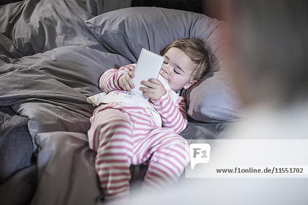 Kleines Mädchen auf dem Bett liegend mit Blick auf das Smartphone