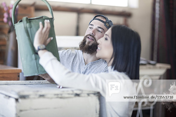 Couple looking at an old watering can in antique shop