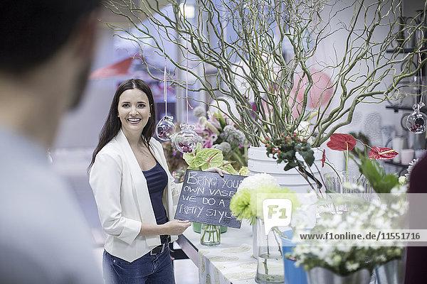 Lächelnde junge Frau im Blumenladen mit Zeichen für den Mann