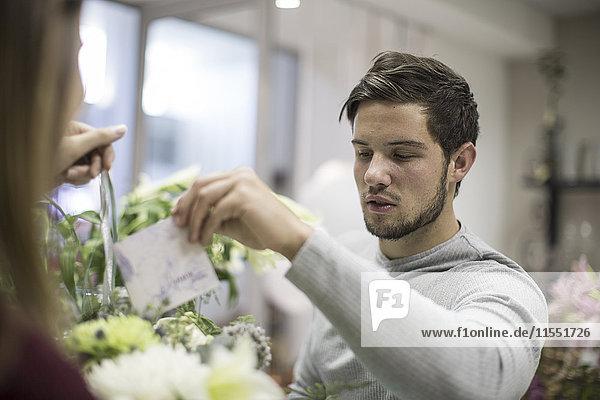 Mann legt Grußkarte in Blumenarrangement