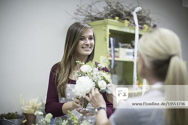 Lächelnder Florist im Blumenladen mit Blumenarrangement