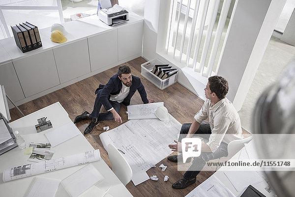 Zwei Männer im Amt besprechen Bauplan