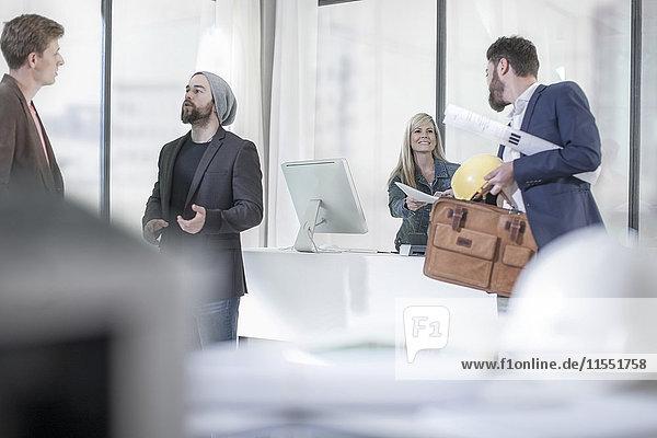 Vier Leute im Büro  die miteinander reden und arbeiten.