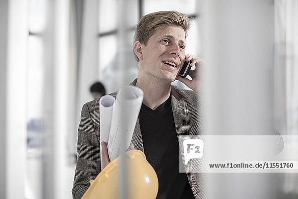 Man holding hard hat talking on phone