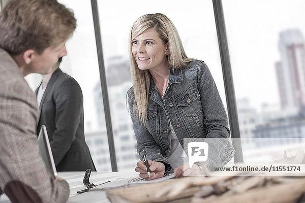 Frau im Gespräch mit Geschäftsmann an der Rezeption