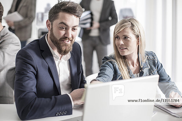 Mann und Frau im Büro mit Blick auf den Laptop