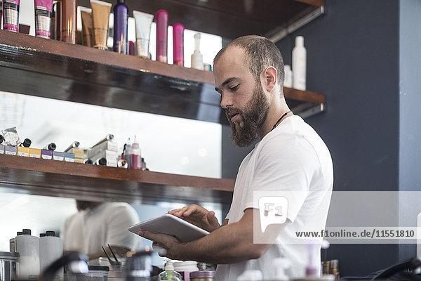 Friseur bei der Shop-Inventarisierung mit digitalem Tablett