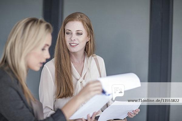 zwei yooun Geschäftsfrauen  die über Dokumente diskutieren.