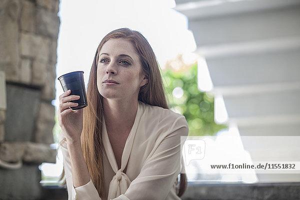 Junge müde Geschäftsfrau beim Kaffeetrinken