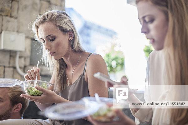 Junge Geschäftsfrauen essen Salat zum Mittagessen