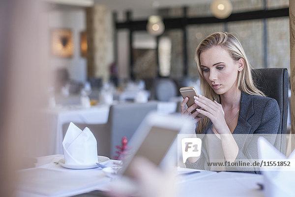 Geschäftsleute mit Smartphones im Restaurant