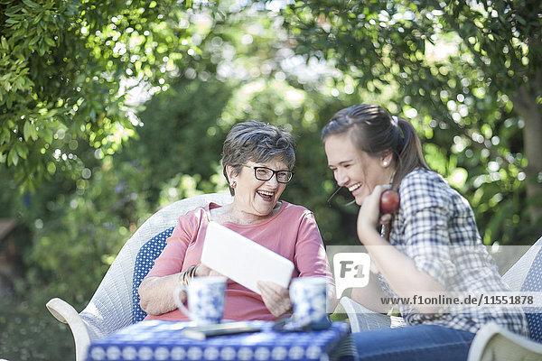 Großmutter und Enkelin im Garten beim gemeinsamen Betrachten des digitalen Tabletts