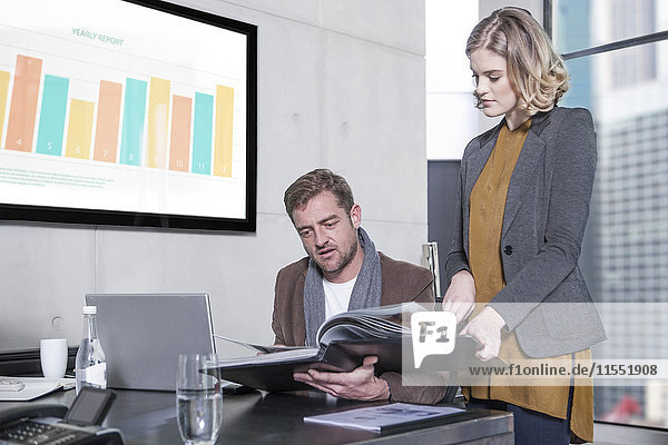Frau zeigt Mappe dem Kollegen im Büro