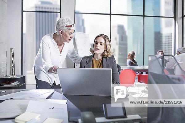 Zwei Frauen im Büro mit Laptop und Besprechung im Hintergrund