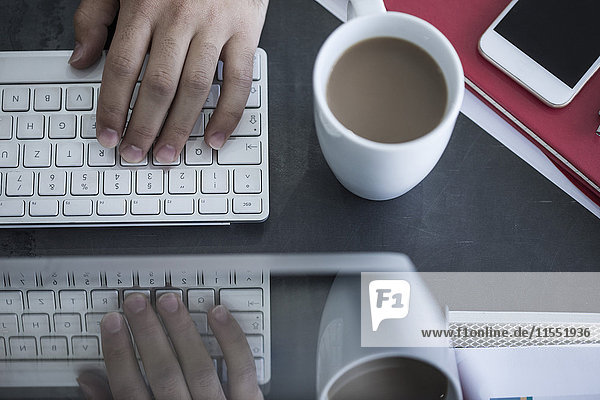 Nahaufnahme des Mannes  der am Computer neben der Kaffeetasse arbeitet.