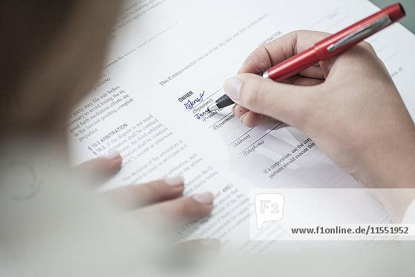 Nahaufnahme einer Frau  die ein Dokument unterschreibt