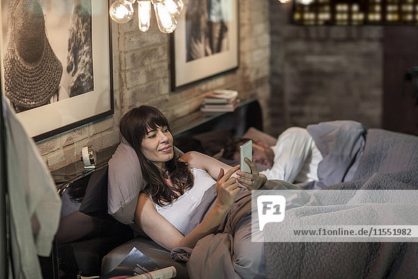 Frau benutzt Handy im Bett mit einem Mann  der neben ihr schläft.
