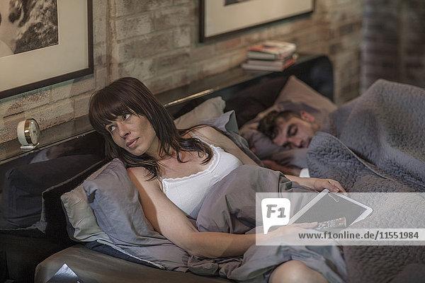 Frau wach im Bett mit Mann neben ihr schlafend