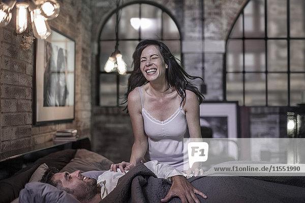 Lachende Frau und Mann im Bett