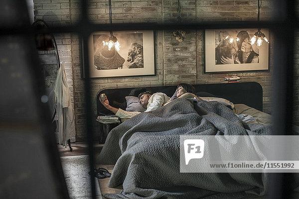 Mann schlaflos im Bett und schaut auf den Wecker  neben ihm liegt seine Frau
