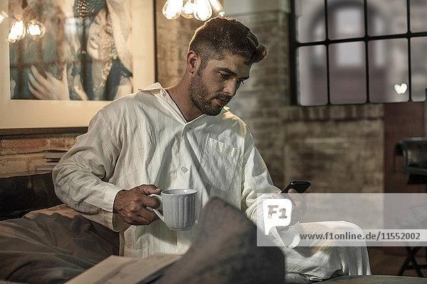 Mann sitzt auf dem Bett und schaut auf das Telefon und trinkt Kaffee.