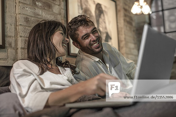 Glückliches Paar im Bett mit Blick auf den Laptop