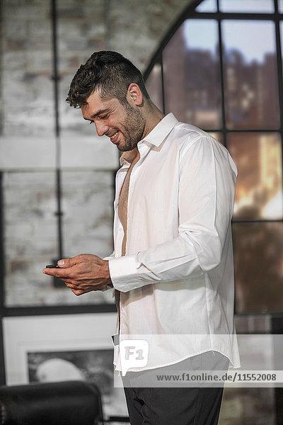 Lächelnder Mann in einer Wohnung  der das Telefon ansieht  während er sich anzieht.