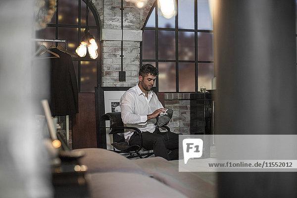 Ein Mann in einer Wohnung  der seine Schuhe putzt.