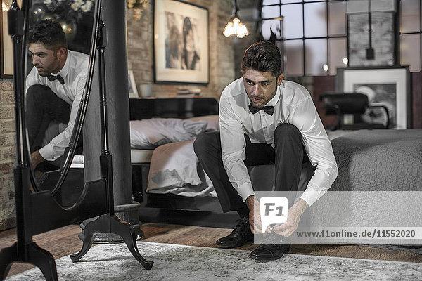 Mann sitzt auf dem Bett und bindet Schuhe.
