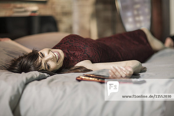 Lächelnde Frau im Abendkleid auf dem Bett