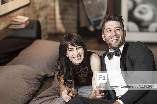 Glückliches Paar in eleganter Kleidung trinkt Champagner im Bett