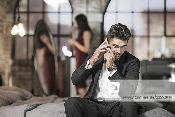 Eleganter Mann im Bett am Telefon mit Frau im Hintergrund