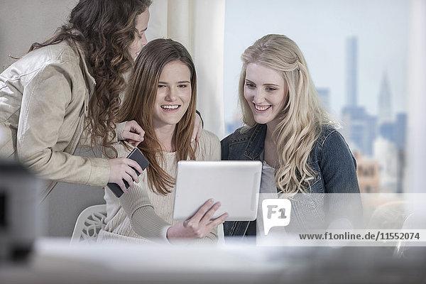 Drei junge Frauen teilen sich ein digitales Tablett
