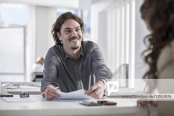 Lächelnder Mann schaut Kollegen im Büro an