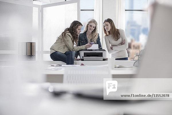 Drei junge Frauen im Büro beim Blick auf das Handy