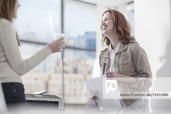 Zwei glückliche Frauen reden im Amt