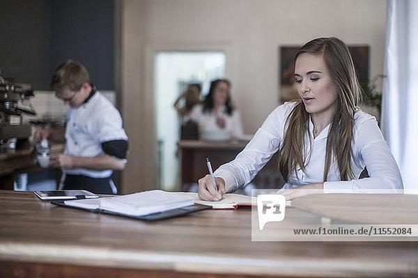 Junge Frau sitzt an der Kaffeebar und arbeitet