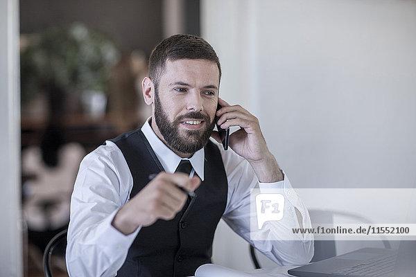 Restaurantleiter im Gespräch am Smartphone