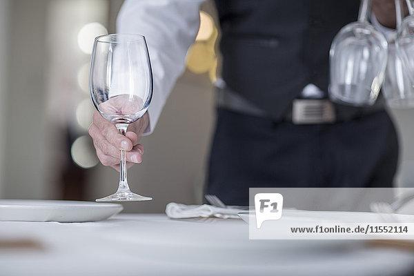 Kellner stellt Weingläser auf den Restauranttisch