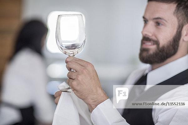 Waiter polishing wine glasses in restaurant