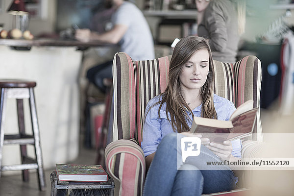 Junge Frau sitzt im Café und liest Buch
