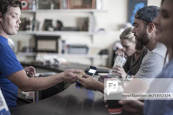 Junger Mann bezahlt mit Kreditkarte im Café