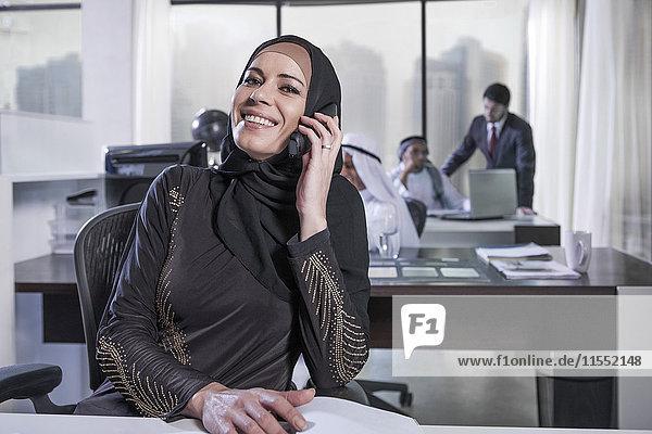 Eine Geschäftsfrau aus dem Nahen Osten im Büro telefoniert.