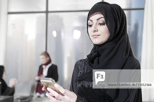 Junge Geschäftsfrau aus dem Nahen Osten im Büro mit Smartphone