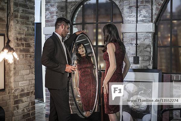 Gut gekleidetes Paar in einer Wohnung mit Frau im Spiegel